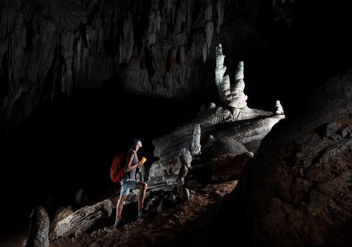 Cavern interior with a person walking uphill using a flash light to shine the way.