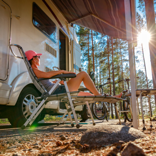 A person sitting outside of their RV enjoying some sun.