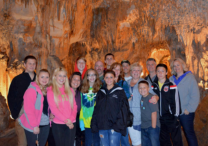 Large group of 16 people looking to the camera with illuminated cave walls behind them.