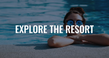 A person standing in a pool with a text overlay that reads Explore The Resort.