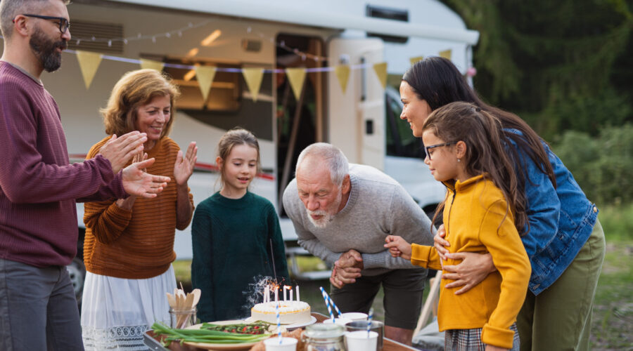 A multi-generation family celebrating birthday outdoors at campsite, caravan holiday trip.